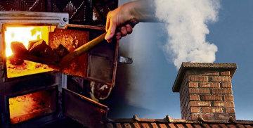 Szufelka dokładająca węgiel do ognia w piecu i dymiący komin